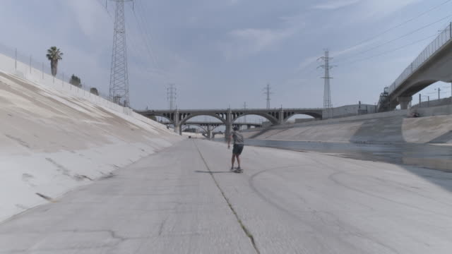 one man skateboarding in the la river - skateboarding stock videos and b-roll footage