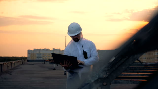 One man types on a laptop, standing near sun panels, close up.