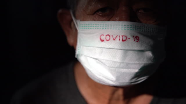 one man wearing a surgical mask with covid-19 text written on it. 2019-ncov virus infection in wuhan city. covid-19 spread around the world. global pandemic risk due to coronavirus outbreak - odzież ochronna filmów i materiałów b-roll