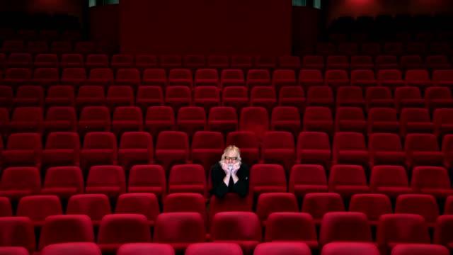 vidéos et rushes de un homme avec barbe blanche se trouve dans le vide cinéma ou théâtre, laissant - cinéma