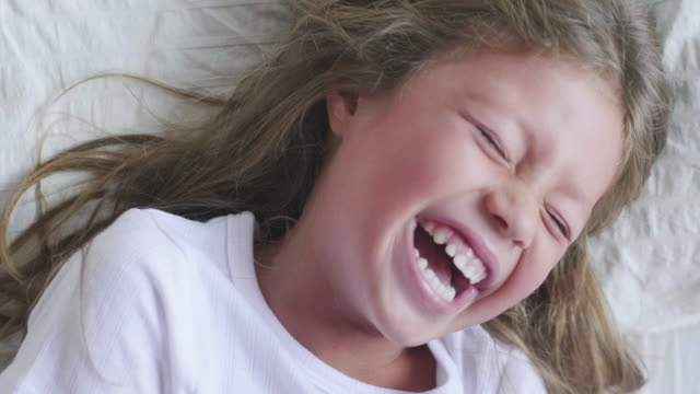 one morning a mother plays tickling her daughter who laughs and just has fun awake. - fare il solletico video stock e b–roll