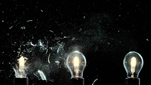 SLO MO one out of three light bulbs exploding Slow motion locked down medium shot of a row of three lit light bulbs. The first from the left explodes and the other two remain intact. Shot on black background. electric light stock videos & royalty-free footage