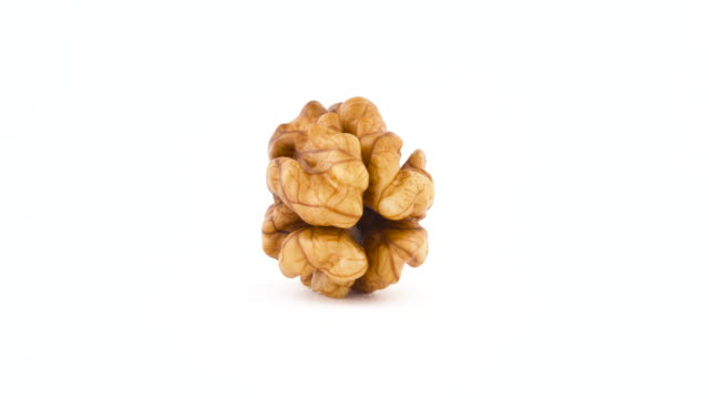 One raw walnut without the shell. Rotating on the turntable isolated on the white background. Close up. Macro.