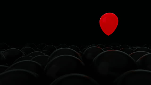 One red balloon is opposed by many other balloons. Dark background. Ideal title text background. One against all. Concept ideas. The concept of personality. Use mask to easy change color.