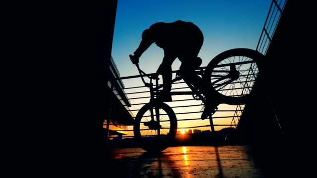 One rider jumps on a bike on a sunset backgrouns, slow motion.