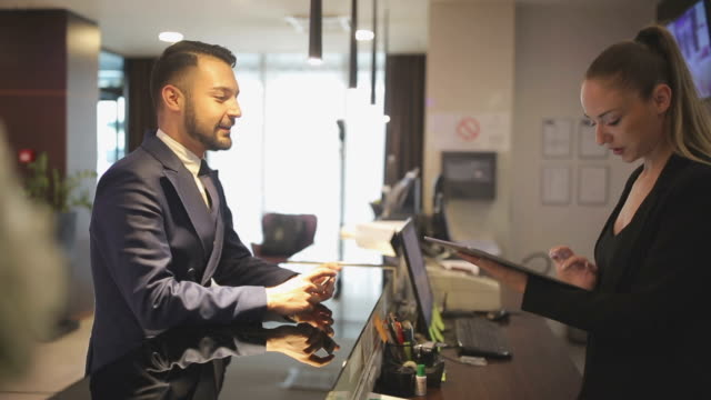 One room please Businessman checking in at the hotel reception checkout stock videos & royalty-free footage