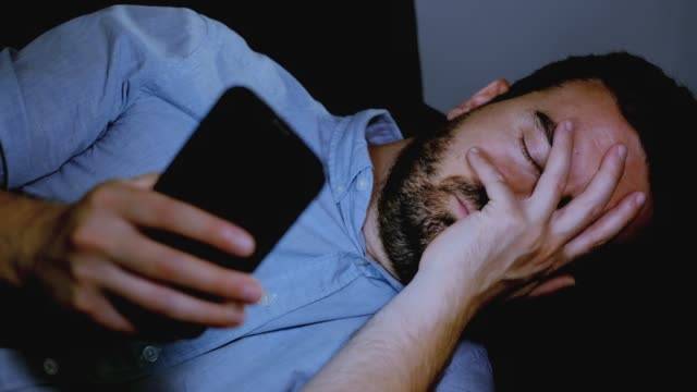 one sad man reading bad news on cellphone - promemoria video stock e b–roll