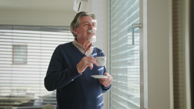 Een senior Kaukasische man koffie drinken en staande naast een raam video