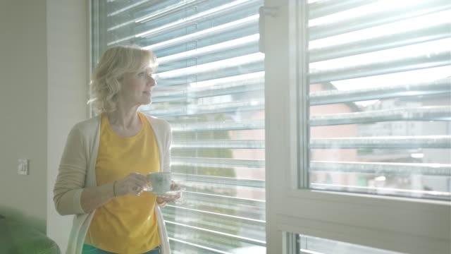 Een senior Kaukasische vrouw koffie drinken en staande naast een raam video