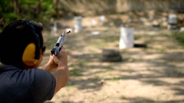 one shot. man shooting semi-automatic pistol to barrel in outdoor field - стрелять стоковые видео и кадры b-roll