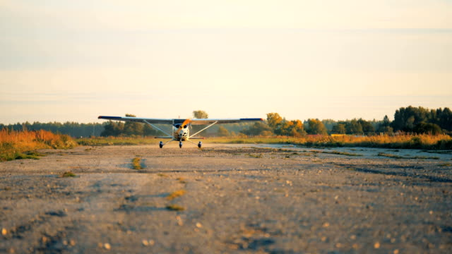 One small airplane going fast on a runway to take off. One small biplane going fast on a runway to take off. 4K. propeller airplane stock videos & royalty-free footage