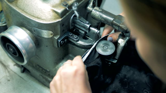 One tailor uses factory sewing machine, close up.