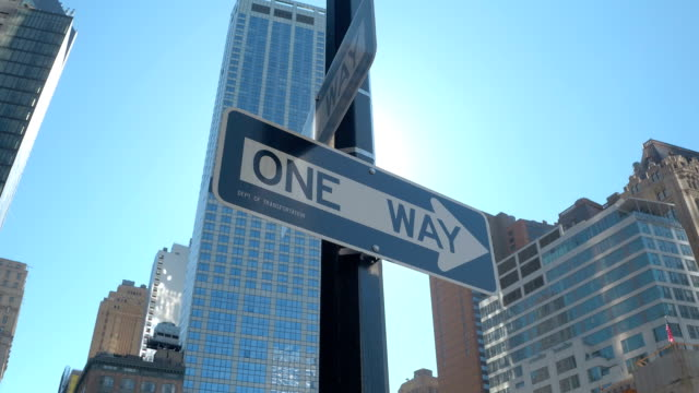CLOSE UP: One way street signs against blue sky on sunny day in New York City video