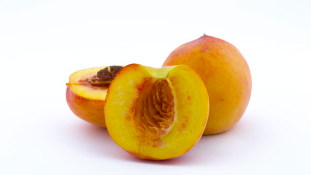 One whole and two halves with the pit of peach fruits. Rotating on the turntable. Isolated on the white background. Close up. One whole and two halves with the pit of peach fruits. Rotating on the turntable. Isolated on the white background. Close up. peach stock videos & royalty-free footage