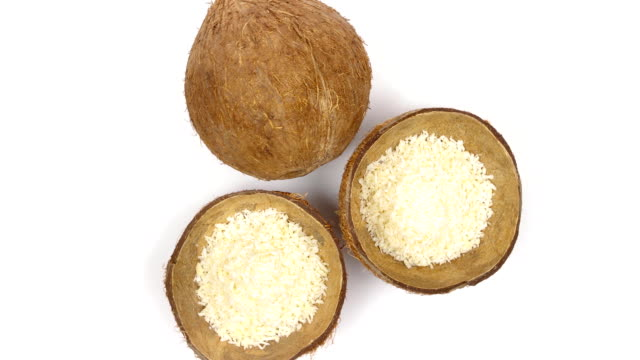 One whole coconut and two shells halves with flakes rotating on white background. Loopable seamless Top view of one whole and two shells halves of tropical coconut with dried white coconut flakes rotating on white isolated background. Healthy tropical fruits. Loopable seamless cocos rotating table top view stock videos & royalty-free footage