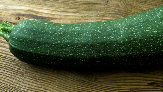 one whole zucchini (cucurbita pepo) on a wooden background - zucchini video stock e b–roll