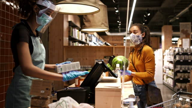 vídeos de stock e filmes b-roll de one woman at the supermarket check out and wearing a protective mask. - supermarket worker
