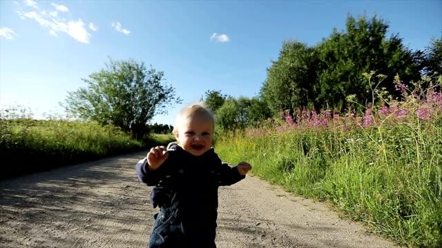 Un año de edad es corriendo por el camino arenoso y riendo. - vídeo