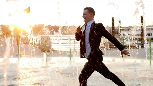 One Young Caucasian Business Man Dancing Outdoors. Running Through Water Fountain at Sunset. Successful, Happiness, Career, Background video