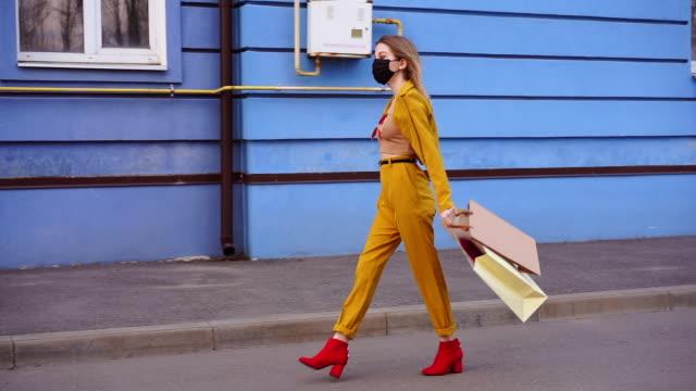 en ung kaukasisk europeisk flicka shopaholic sitter på gatan med inköp i paket. - face mask bildbanksvideor och videomaterial från bakom kulisserna