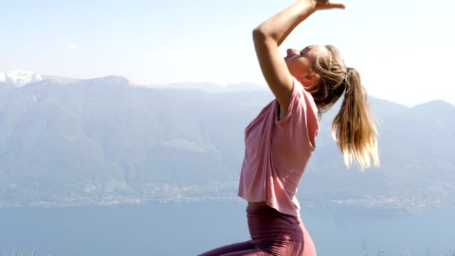One young woman exercising yoga on mountain top in Spring. People wellbeing relaxation healthy lifestyle concept. Shot in Ticino Canton, Switzerland.