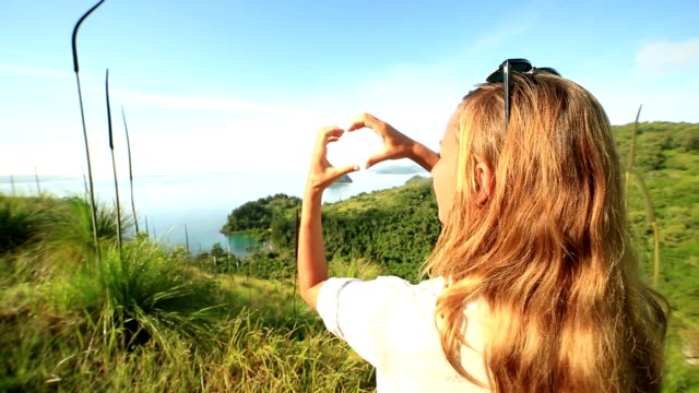 One young woman makes heart shape finger frame to seascape