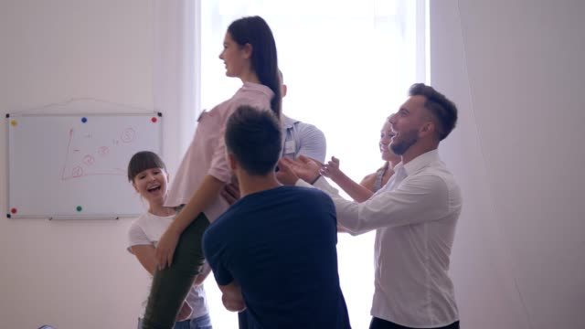 сonfidence and trust, girl falls on back and colleagues catch her and then applaud on group therapy - fiducia video stock e b–roll