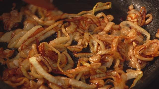vídeos y material grabado en eventos de stock de los anillos de cebolla se fríen y caramelizan en azúcar en la sartén - cebolla