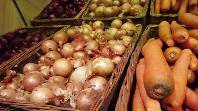 Onions, carrots and potatoes on shelves in the supermarket. video