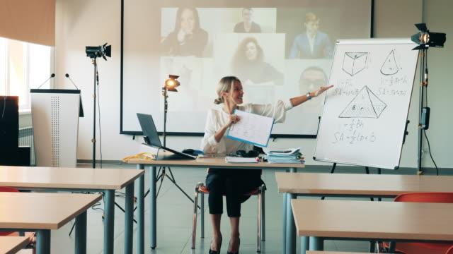 オンラインクラス、リモート学習コンセプト。女性は空のクラスで彼女のオンラインレッスン中に式を説明しています - 人里離れた点の映像素材/bロール