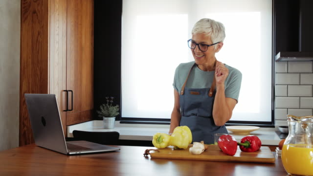 Online cooking tutorials are her favorite Senior woman preparing delicious lunch in the kitchen with the help of technology recipe stock videos & royalty-free footage