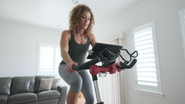Online Exercise Coach in Home A woman exercising on a spin bike using an online instructor inside her home. exercise bike stock videos & royalty-free footage
