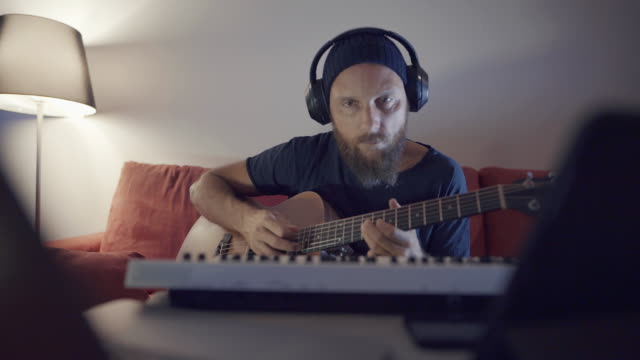 Online guitar teacher in video chat at laptop teach guitar during videoconference, home office
