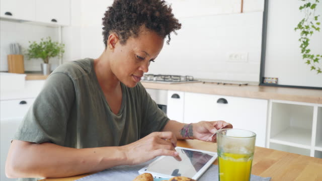 Online payment is easy! Black woman doing online payment using a digital tablet. She is in the kitchen having her breakfast. Online payment has never been so easy! shopping online stock videos & royalty-free footage