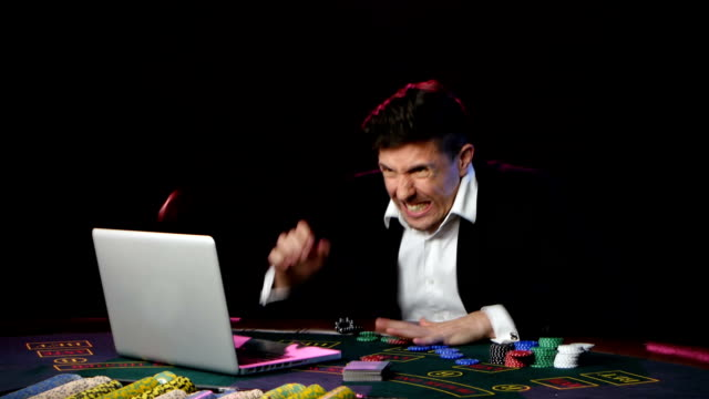 Online poker player losing with playing cards, chips and laptop. Close up video
