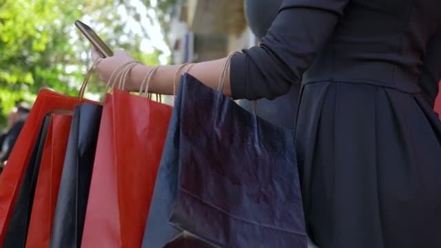 vídeos y material grabado en eventos de stock de compras en línea, chica de compras utiliza teléfono móvil para comprar y pagar en internet en venta estacional, muchas bolsas colgadas por lado - black friday sale
