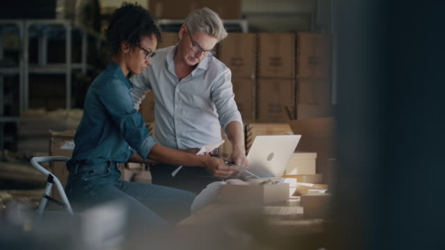 Online selling business partners working together Two business partners discussing while preparing a package to deliver. Business man and woman working together at warehouse for online seller business. employee engagement stock videos & royalty-free footage
