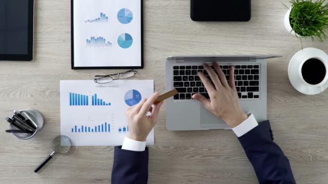 online-shopping, geschäftsmann, einfügen von kartennummer auf laptop im büro, finanzen - billionär stock-videos und b-roll-filmmaterial