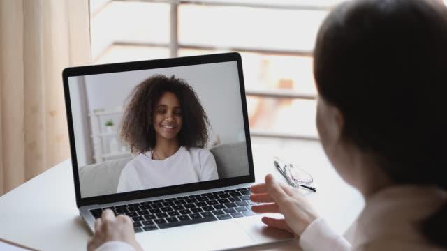 Online teacher or psychologist webcam conferencing with african school girl