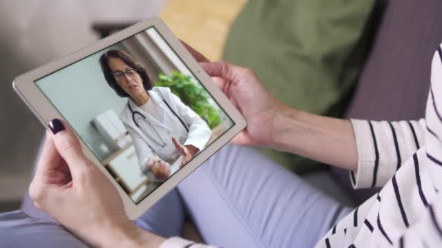 Online video call via tablet female doctor in white lab coat consulting her patient