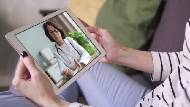 online videosamtal via tablett kvinnlig läkare i vit lab coat samråd med sin patient - videor med medicinsk undersökning bildbanksvideor och videomaterial från bakom kulisserna
