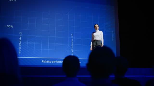 on-stage erfolgreiche weibliche sprecherin präsentiert technologisches produkt, verwendet fernbedienung für präsentation, anzeigen von infografiken, statistik animation auf dem bildschirm. live event / gerätefreigabe. zeitlupe - zuschauerraum stock-videos und b-roll-filmmaterial
