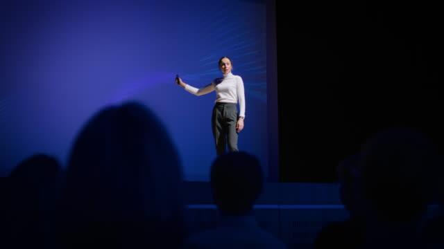framgångsrik kvinnlig högtalare på scenen presenterar teknisk produkt, använder fjärrkontroll för presentation, visar infografik, statistikanimering på storskärm. live event / business conference - affärskonferens bildbanksvideor och videomaterial från bakom kulisserna