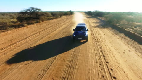 Onwards to desert adventure 4k video drone footage of a truck driving along a dirt road through the Namibian desert extreme terrain stock videos & royalty-free footage