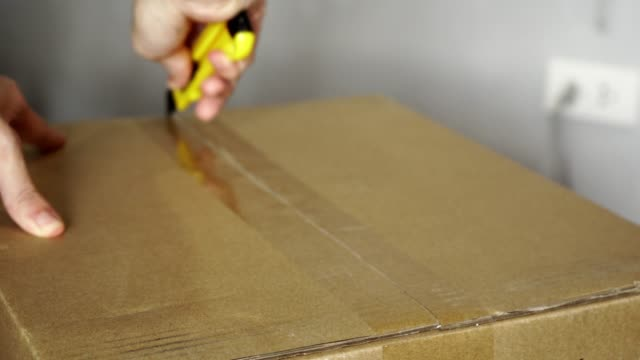 Open a sealed cardboard box with utility knife