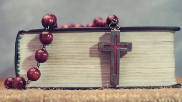 Open Bible and the crucifix beads on a golden table, close up. Beautiful dark background. Religion concept