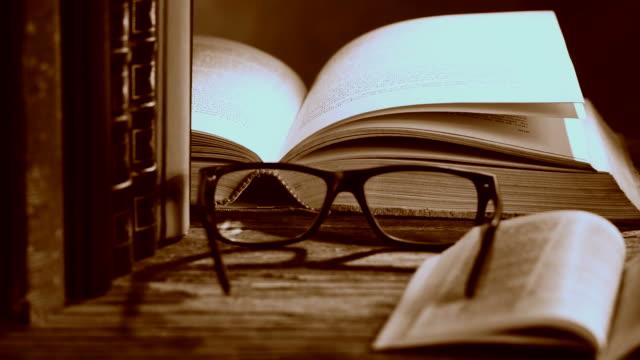 stockvideo's en b-roll-footage met open bijbel met glazen en boeken. - boekenkast