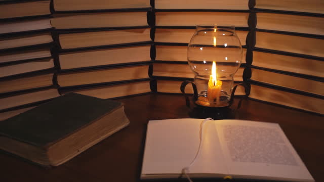 libro aperto e candela accesa - candeliere video stock e b–roll