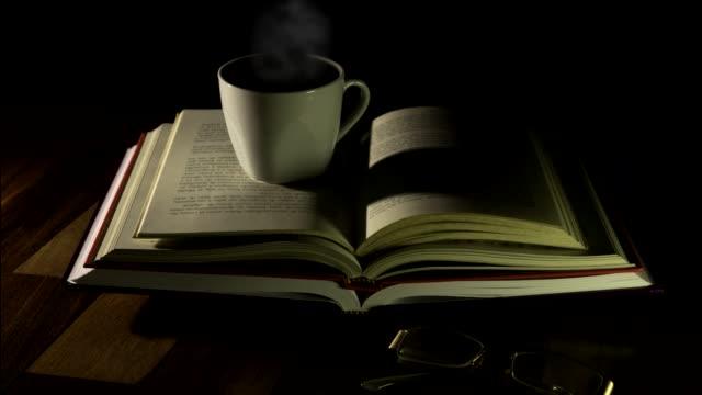 stockvideo's en b-roll-footage met open boeken, een kop koffie en glazen op houten lijst - boekenkast