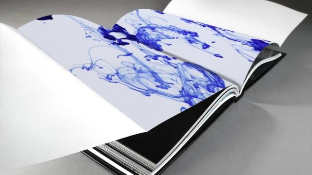 stockvideo's en b-roll-footage met open boek pagina op grijze achtergrond met de abstracte kunst in beweging - magazine mockup